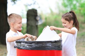 Little kids throwing garbage into litter bin outdoors
