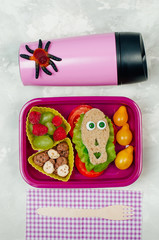 Open Halloween lunch box with school lunch with near thermo mug and fork on grey concrete background