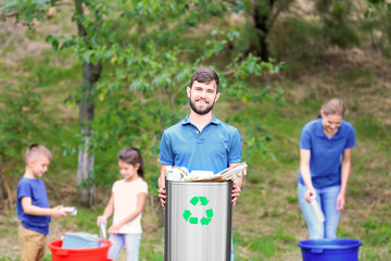 Family collecting garbage outdoors. Recycling concept