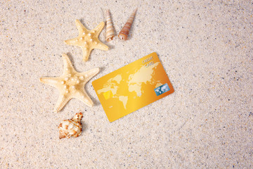 Credit card with shells on sand