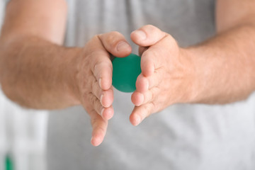 Senior man doing exercises with rubber ball on blurred background