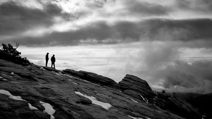 Two men look out into the clouds on a summit