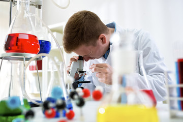 Young scientist working with microscope at the clinic laboratory