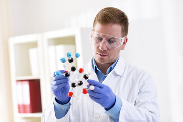 Young scientist holding molecular model