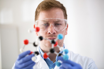 Young scientist holding molecular model at private clinic