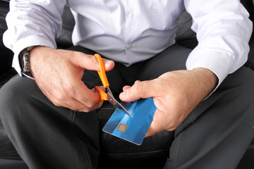 Adult man hands cutting a credit card with a pair of scissor