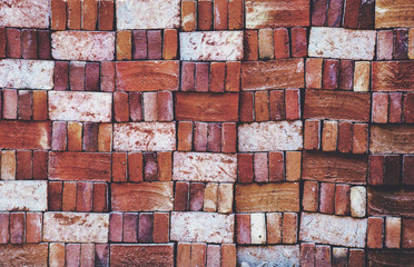 Pile of locally produced and neatly arranged red bricks creates a pattern