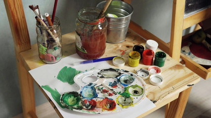 Palette, watercolors and brushes on a wooden chair