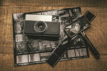 Old analog camera, film, magnifying glass and contact sheet over wooden table.