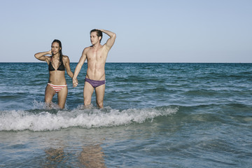 Young Man and Woman Couple in Bikini and Trunks Swimwear Coming Out of Water at the Beach in Summer