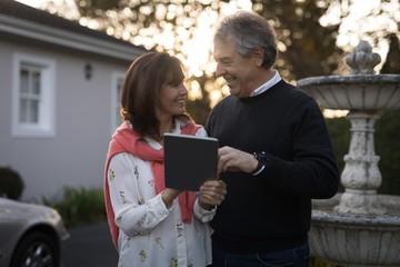 Senior couple using digital tablet outdoors