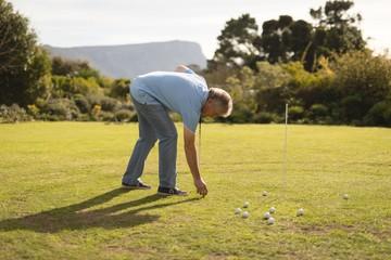 Senior man placing golf ball