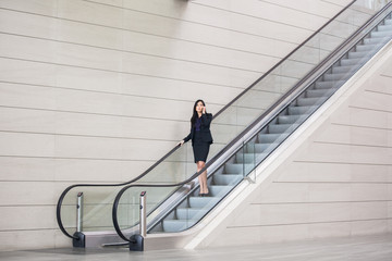 Asian businesswoman talking on her cell phone while going down on an escalator