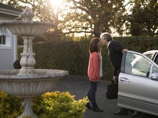 Senior couple kissing near the car