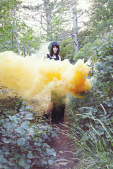 Beautiful woman standing in yellow smoke in the forest
