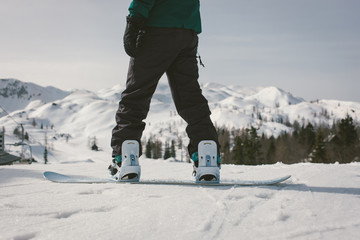 Snowboarder at the top of a ski slope ready to snowboard.