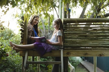 Girl reading book with her grandmother while sitting on tree house