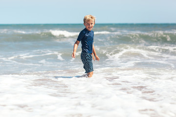 smiling boy playing in the ocean