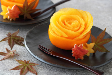 Persimmon rose in hollowed-out persimmon with maple leaves on black plate