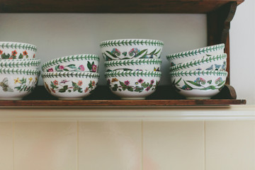 Detail of flowered china bowls in piles on wooden shelf