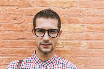 Portrait of a young entrepreneur in front a brick wall.