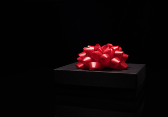 Black gift box on a black surface with big red bow. Close up. Celebrate concept, New Year, Merry Christmas, Anniversary,Birthday,Valentines day,men,women, winter holidays.