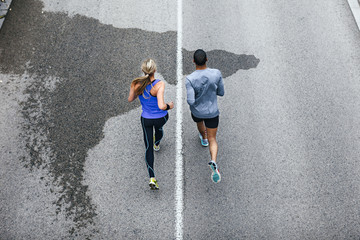 Aerial view of young couple running on a urban road.