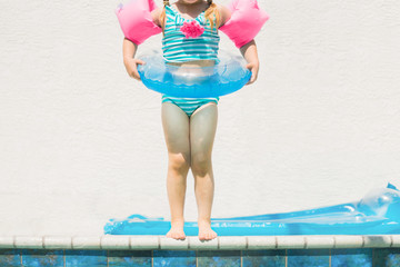 Little Girl Stands at the Edge of the Pool Ready to Jump In