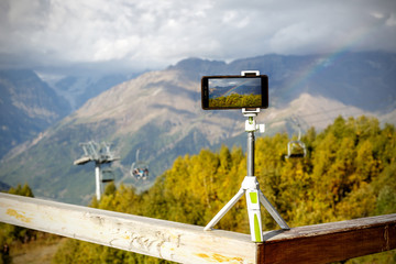 smartphone on a tripod in the mountains, a lift and a rainbow on the background.