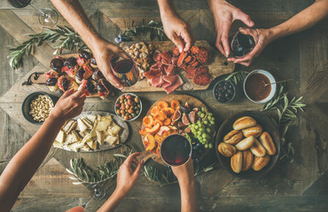 Flat-lay of friends hands eating and drinking together. Top view of people having party, gathering, celebrating together at vintage wooden rustic table set with different wine snacks and fingerfoods