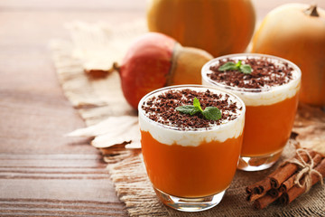 Pumpkin smoothie in glasses with cinnamon on wooden table