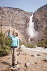 Woman taking a selfie near the waterfall