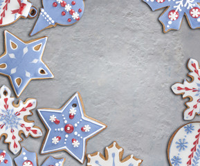 Snowflake-shaped gingerbread cookie on concrete background. Decorated with royal icing in white, red and blue. Top down view.