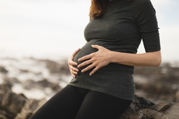 Midsection of pregnant woman touching her belly