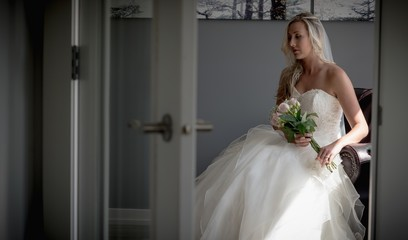 Bride sitting with flower bouquet at home