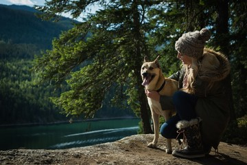 Woman with dog relaxing near river