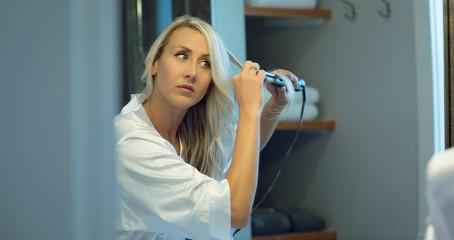 Beautiful woman using straightener