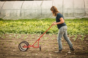 Female farmer using power weedier in the field