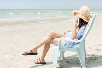 woman with hat relax in the sun on their deck chairs in the beach. Traveling, vacation, concept.