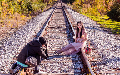 A young oriental girl is getting picture taken by a enthusiastic photographer
