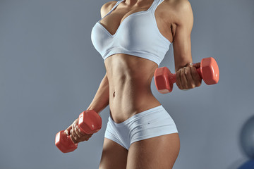 Sexy woman doing exersise with dumbells