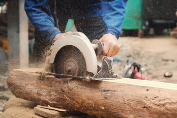 carpenter using saws  cutting woods at construction site