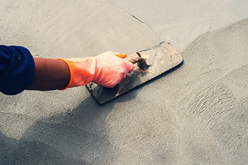 close up hand worker leveling concrete pavement for mix cement at construction site
