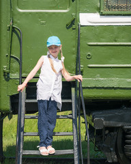 The girl in the blue baseball cap on the steps of an old wagon.
