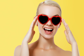Valentine's Day concept. Fashion Model girl isolated over yellow background. Beauty stylish blonde woman posing in heart shaped sunglasses. Casual style with beauty accessories. High fashion style