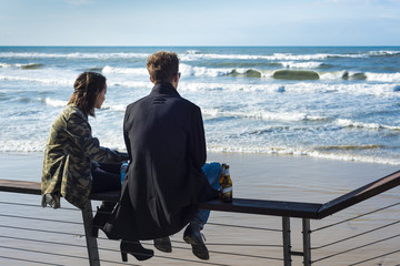 Beautiful couple sitting on a handrail and looking at the sea. Jaffo Beach, Old Jaffa, Israel.