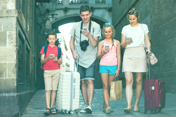 Wife with husband and children are looking in phones