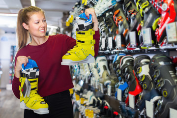 Cheerful female is choosing stylish boots for skiing
