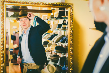 Girl and male try on modern hats at the boutique