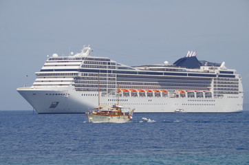 Cruise ship with sailing boat